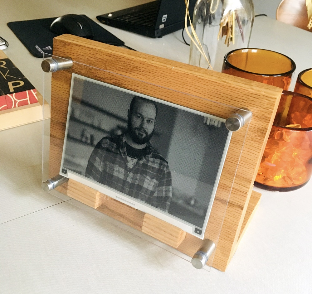 e-paper frame made of wood, clear acrylic, and a metal standoff in each corner