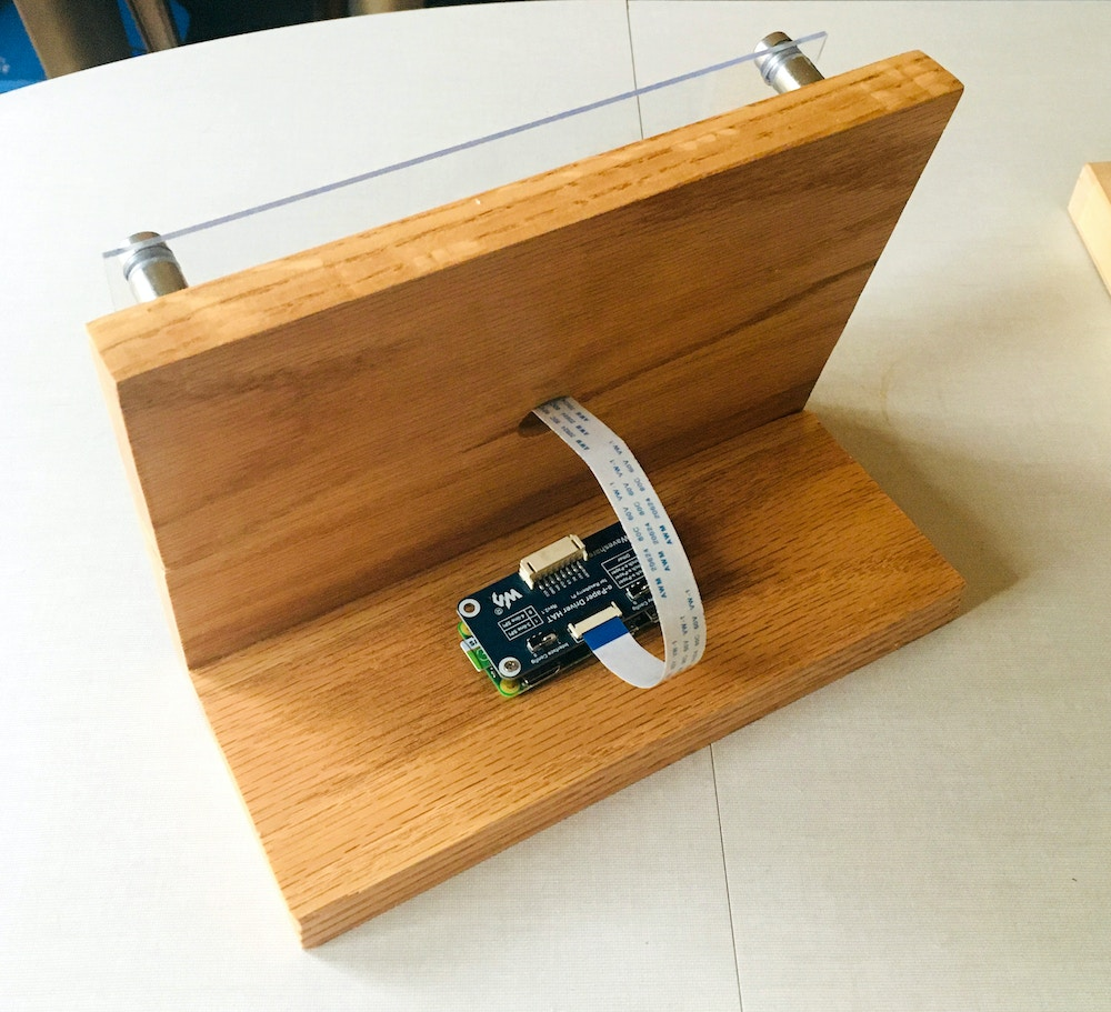 Back of the wooden frame, cable coming through the hole, connected to the raspberry pi